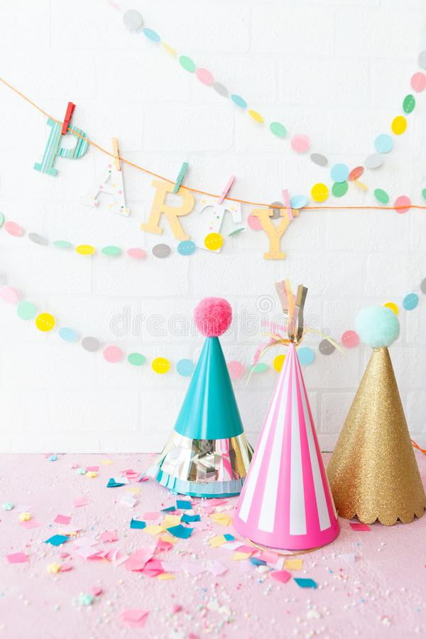 Colorful party props. Colorful party hats and cheerful garlands and decorations stock photos