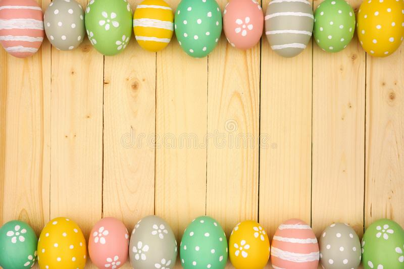 Colorful pastel Easter Egg double border against a natural wood background stock images
