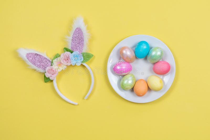Cute bunny ears and colorful Easter eggs on yellow background royalty free stock photos