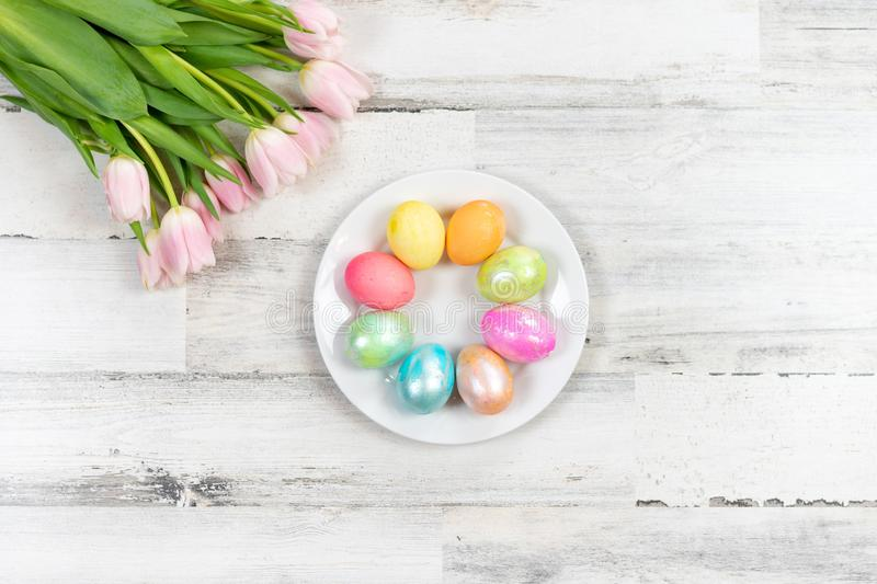 Colorful pastel Easter eggs and pink tulips stock photo