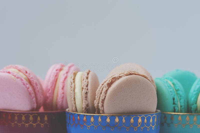 Colorful pastel macaroons in vintage coffee cups stock photography