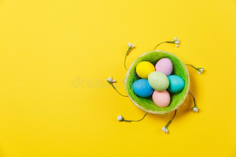 Colorful pastel painted Easter eggs in basket with green grass, white flowers lilies of the valley isolated on yellow stock photography
