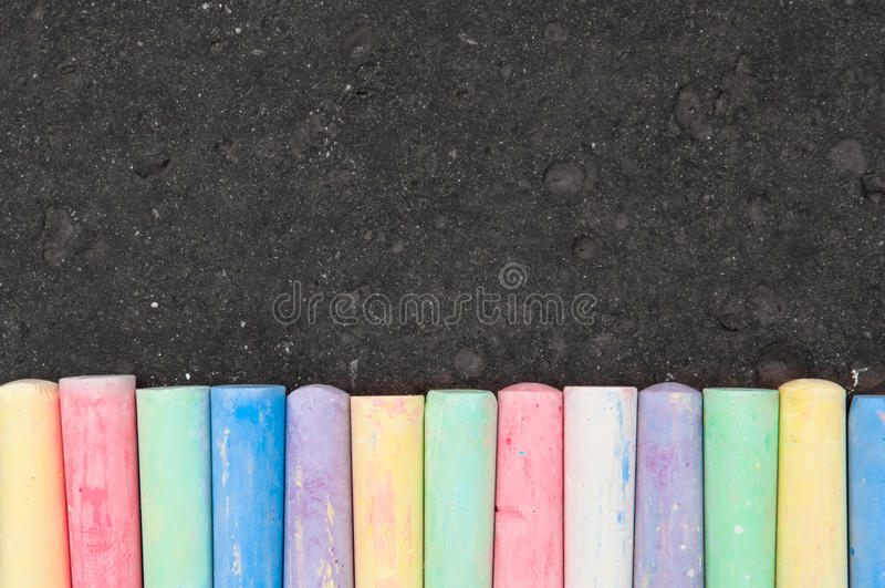 Colorful pastel sidewalk chalk on dark asphalt background. Top view royalty free stock photo