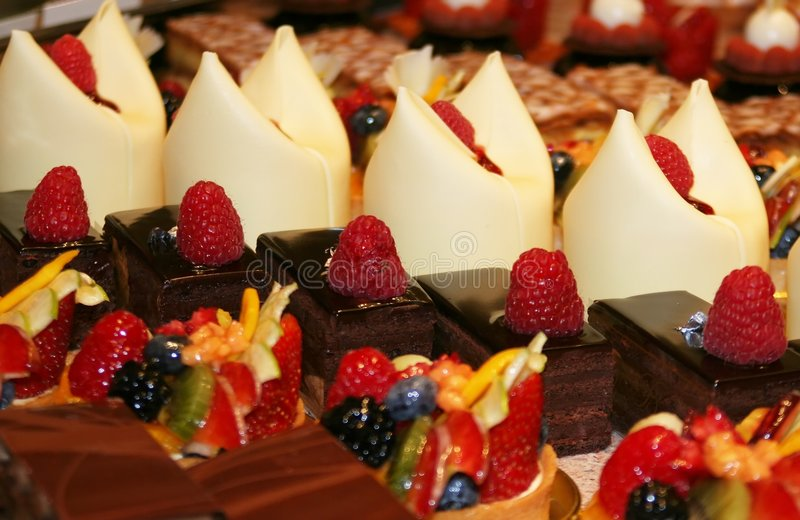 Colorful pastries. A variety of chocolate pastries decorated with fruit royalty free stock photography
