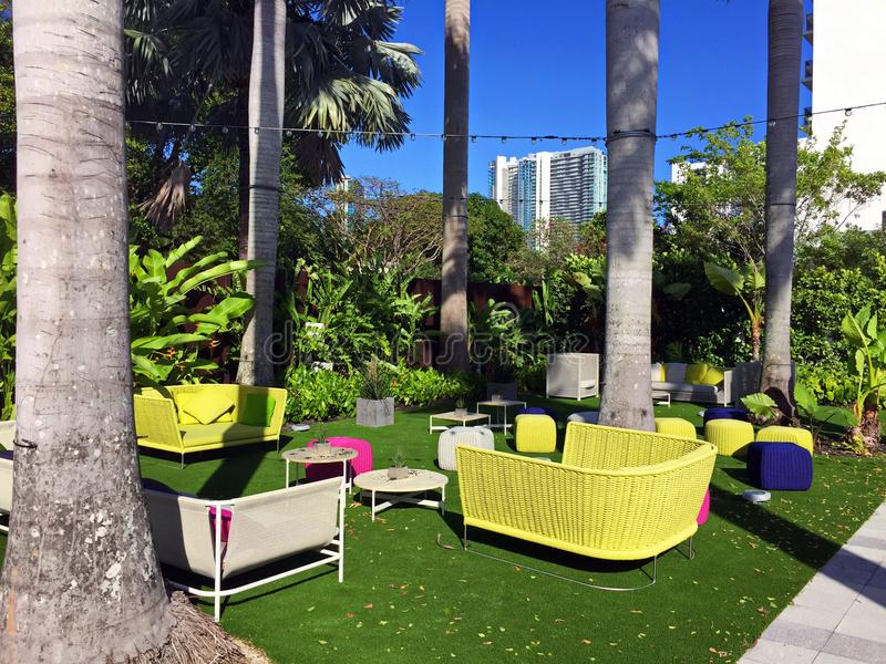 Colorful Patio Furniture in Tropical Setting. Brightly colored lounge furniture outside on the back patio of Plant Food & Wine in Miami, Florida. Flourescent royalty free stock images