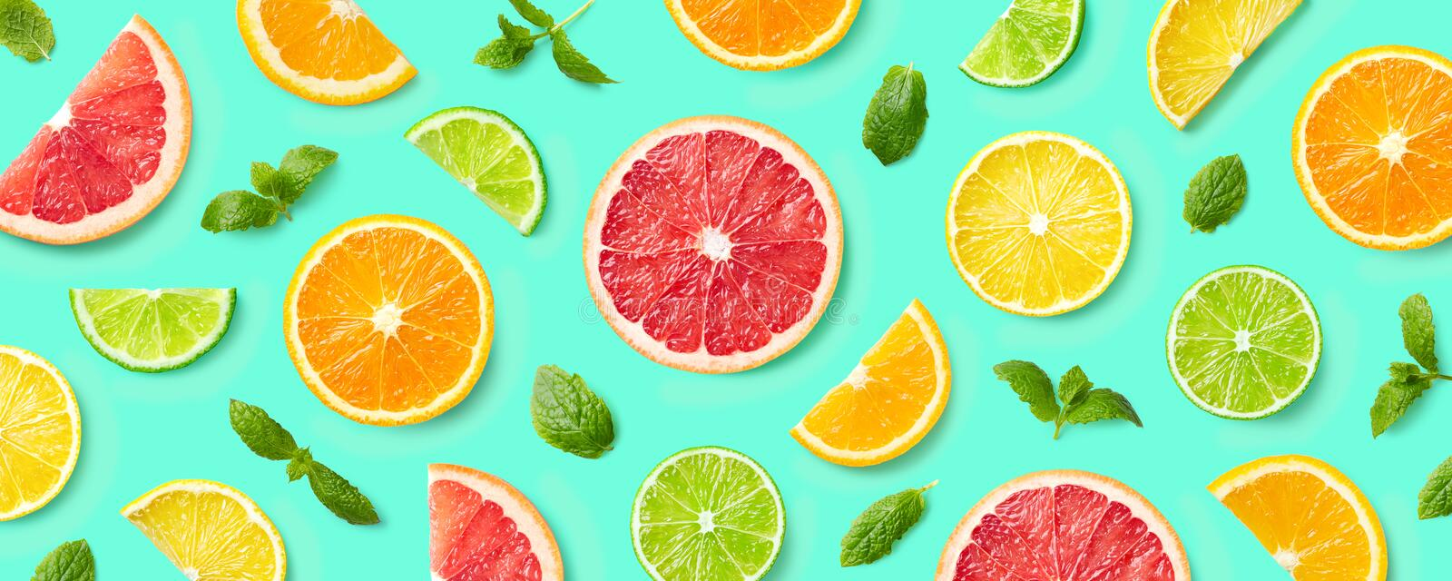 Colorful pattern of citrus fruit slices and mint leaves royalty free stock photo