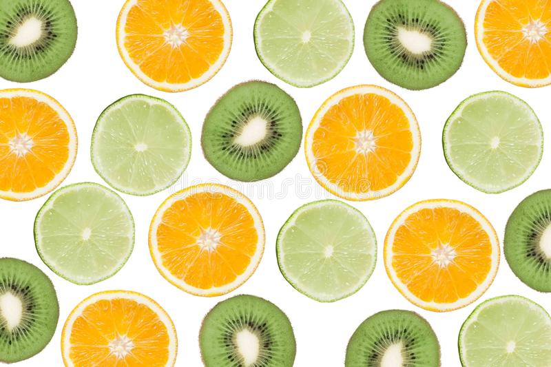Colorful pattern of kiwi, lime and oranges. Top view of the citrus fruits and sliced kiwi. On white background. stock photos
