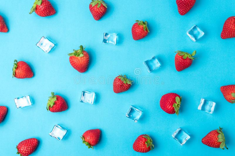 Colorful pattern made of strawberries with ice cubes on blue background. Minimal summer concept royalty free stock image