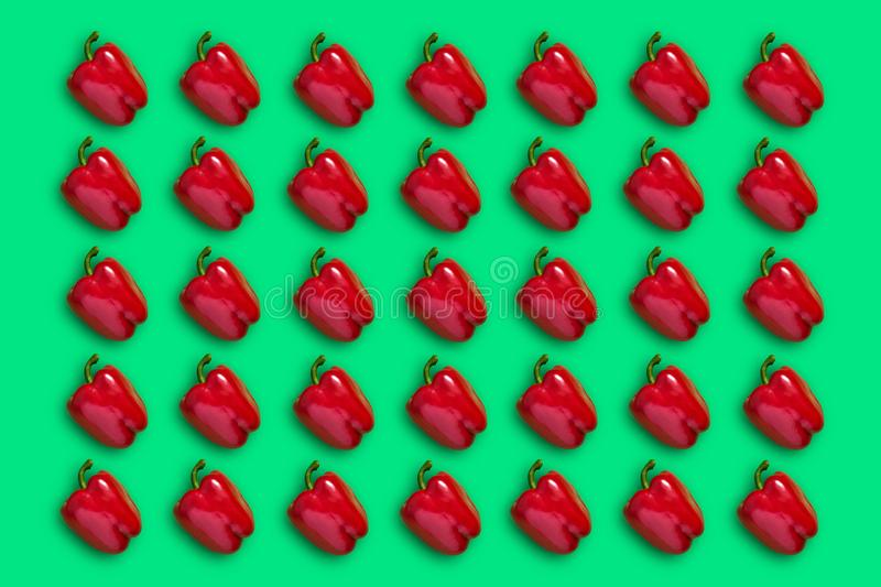 Colorful pattern of red bell pepper on a green background. Creative food concept. stock photography