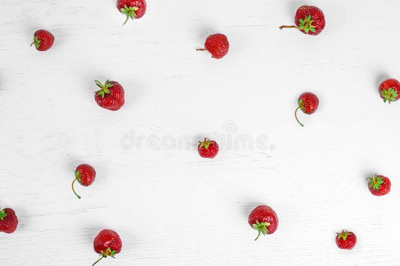Colorful pattern of strawberries on white wood background. Top view stock photo