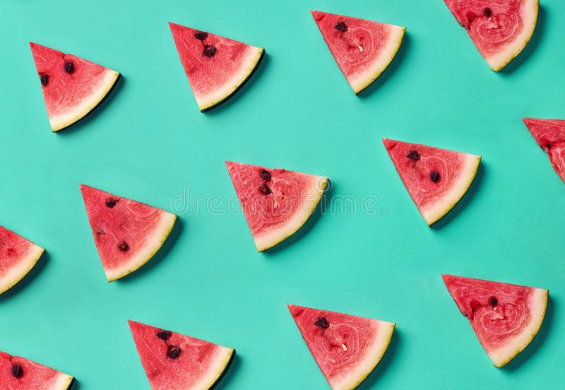 Colorful pattern of watermelon slices. Colorful fruit pattern of fresh watermelon slices on blue background. From top view royalty free stock photo