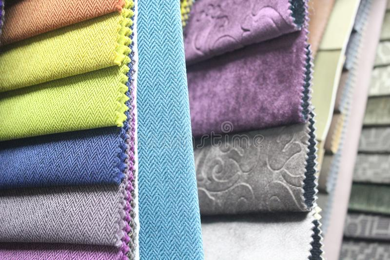 Colorful patterns of upholstery fabric. Close-up of samples of furniture fabric. Multicolored soft velour. Furniture industry. Bac. Kground texture. Fabric royalty free stock photography