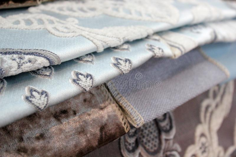 Colorful patterns of upholstery fabric. Close-up of samples of furniture fabric. Multicolored soft velour. Furniture industry. Bac royalty free stock photos