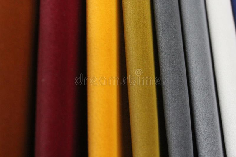 Colorful patterns of upholstery fabric. Close-up of samples of furniture fabric. Multicolored soft velour. Furniture industry. Bac. Kground texture. Fabric stock photo