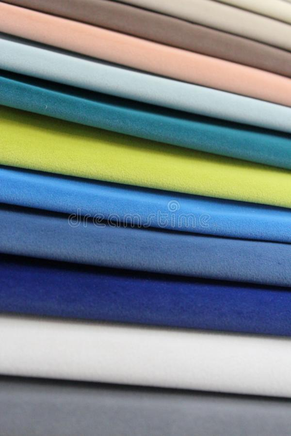 Colorful patterns of upholstery fabric. Close-up of samples of furniture fabric. Multicolored soft velour. Furniture industry. Bac. Kground texture. Fabric stock image