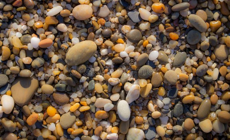 Colorful pebbles on beach. Pebbles closeup background. Small round stones in sunlight. Minerals concept. royalty free stock photography