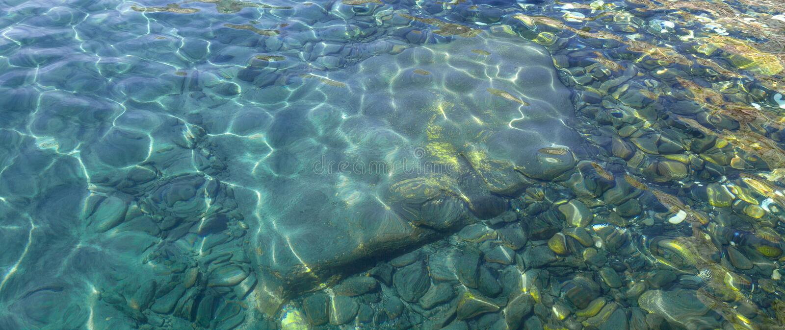 Colorful pebbles and big stone under clear water stock image