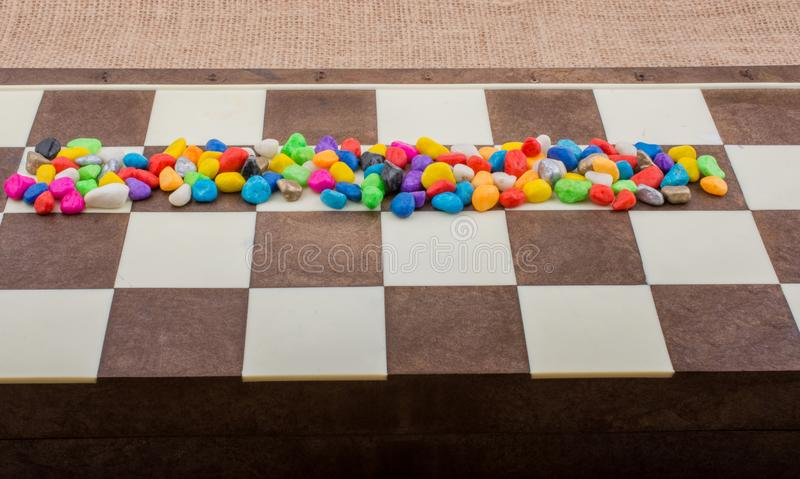 Colorful pebbles spread on checked board royalty free stock images
