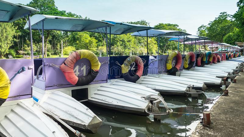 Colorful pedal boats parked in a long line stock images