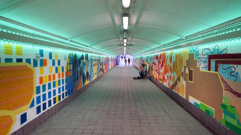 A colorful pedestrian tunnel in Singapore. A colorful pedestrian tunnel crossing a busy road above near the Singapore River. The tunnel is brightly lit and very stock images