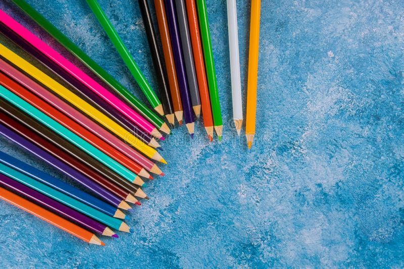 Colorful pencils on blue background. Top view stock photography