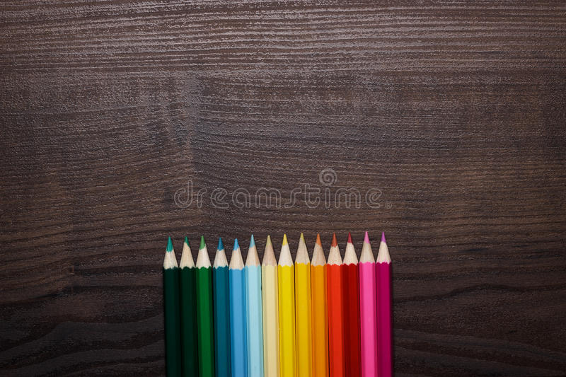 Colorful pencils over brown table background royalty free stock image