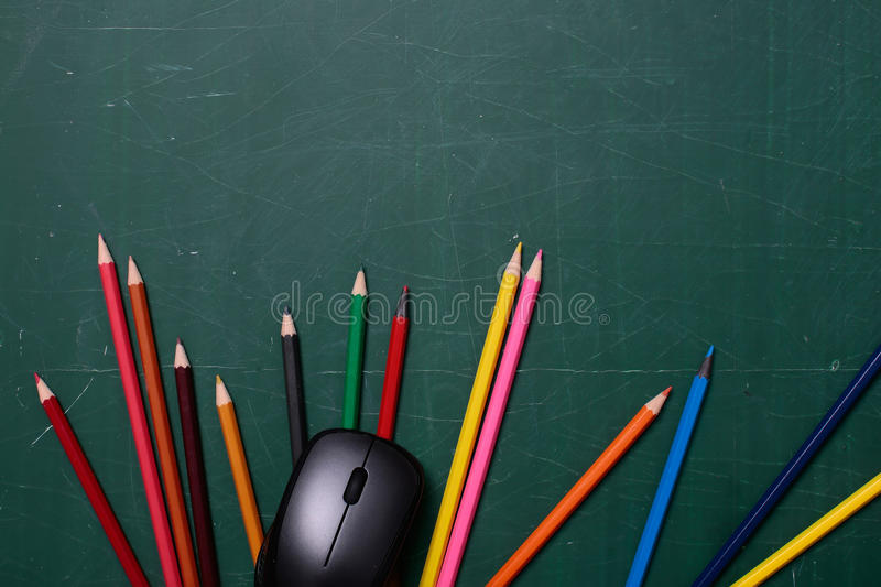 Colorful pencils and computer mouse on desk. Many colorful stationary of pencils for drawing or painting art different colors laying on green school blackboard royalty free stock images