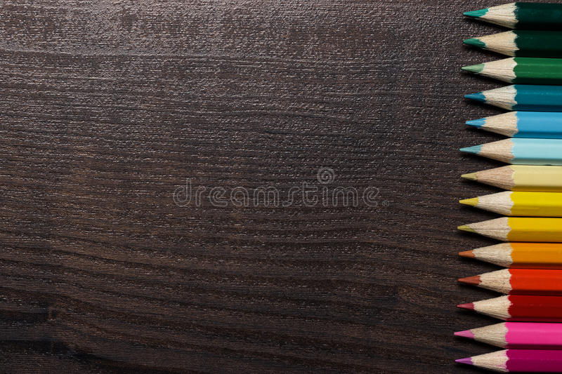 Colorful pencils on dark brown table background royalty free stock photography