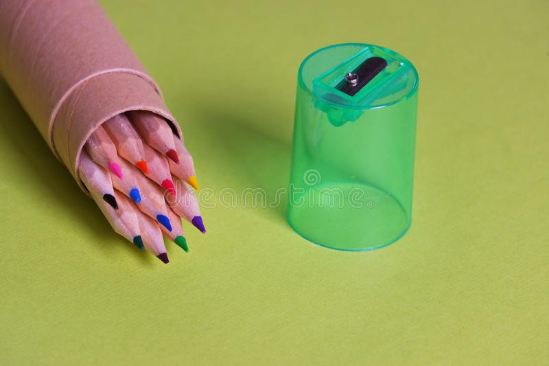 Colorful pencils green plastic sharpener cardboard holder. Colorful set sharpened pencils in cardboard holder green plastic sharpener yellow backbround side view stock images