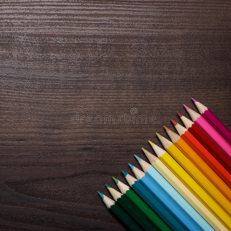 Colorful pencils over brown table background royalty free stock photos