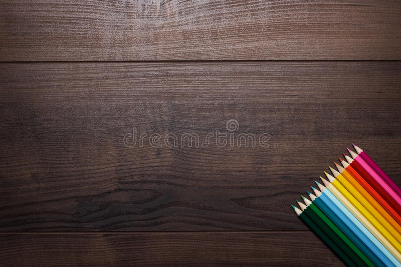 Colorful pencils over brown wooden table stock photos