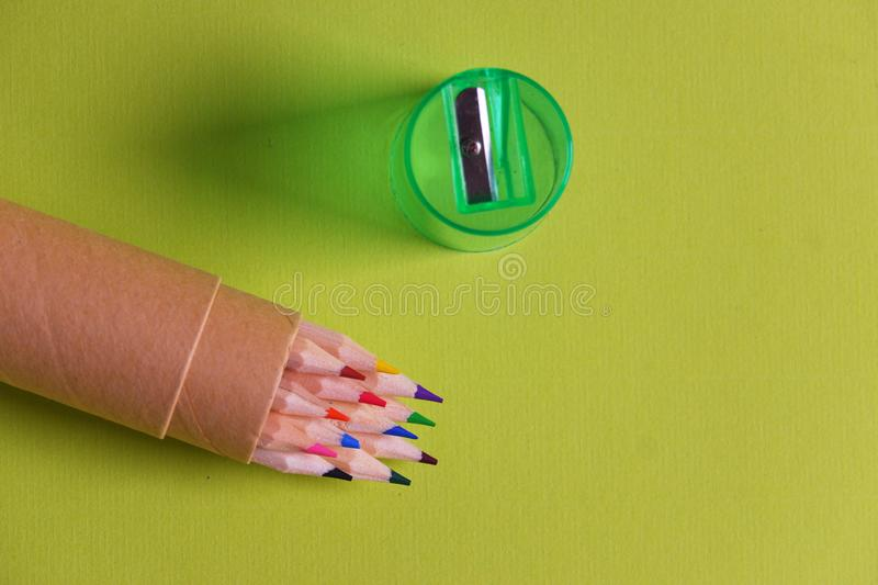Colorful pencils and sharpener yellow background. Colorful set sharpened pencils in cardboard holder green plastic sharpener yellow backbround top view royalty free stock photo