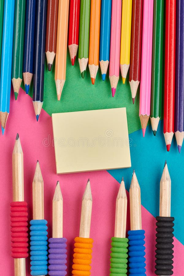 Colorful pencils and sticky note paper. stock photo