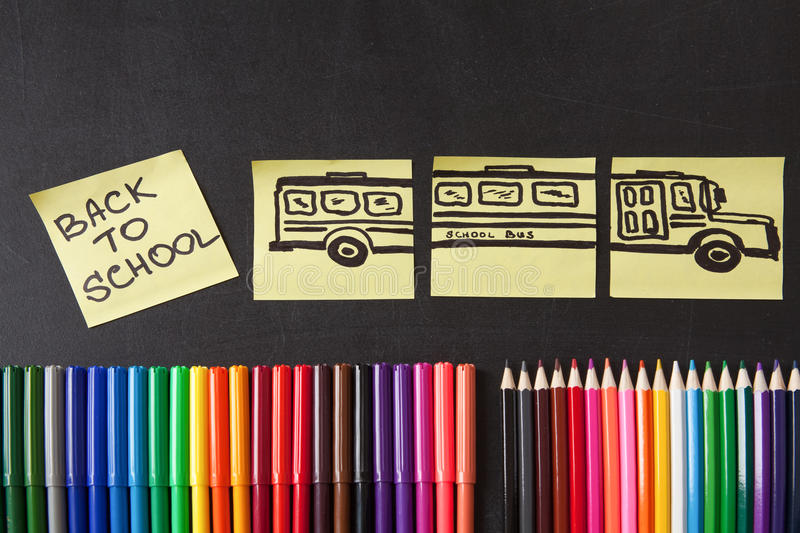 Colorful pencils, titles Back to school and school bus drawn on the pieces of paper on the chalkboard. Back to school background with a lot of colorful felt-tip royalty free stock photo