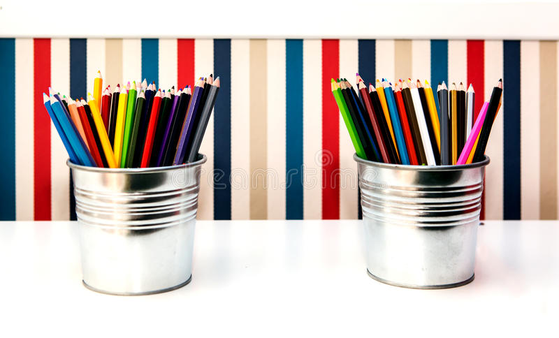 Colorful pencils in two pails on background. Colorful pencils in two pails on vertical stripes background stock photography