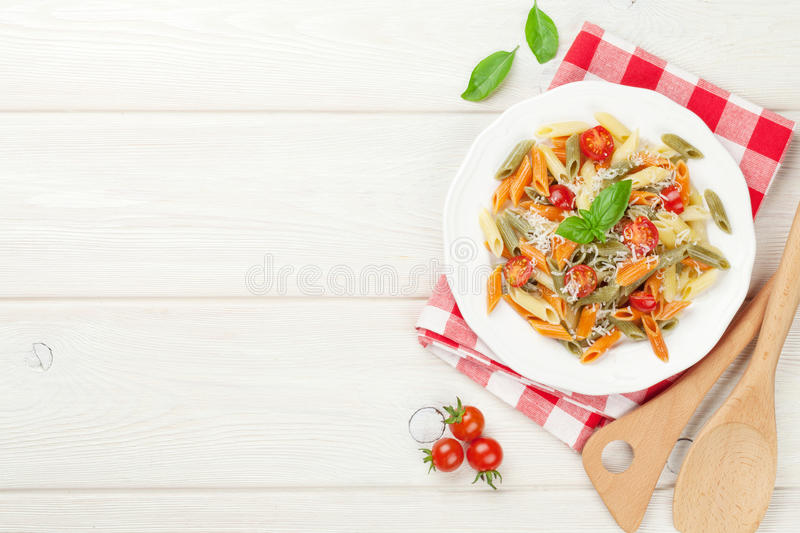 Colorful penne pasta with tomatoes and basil stock images