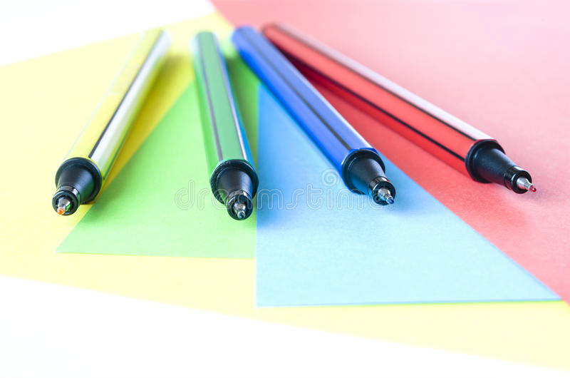 Colorful Pens. Arranged on colorful paper background. Selective focus on blue pen royalty free stock images