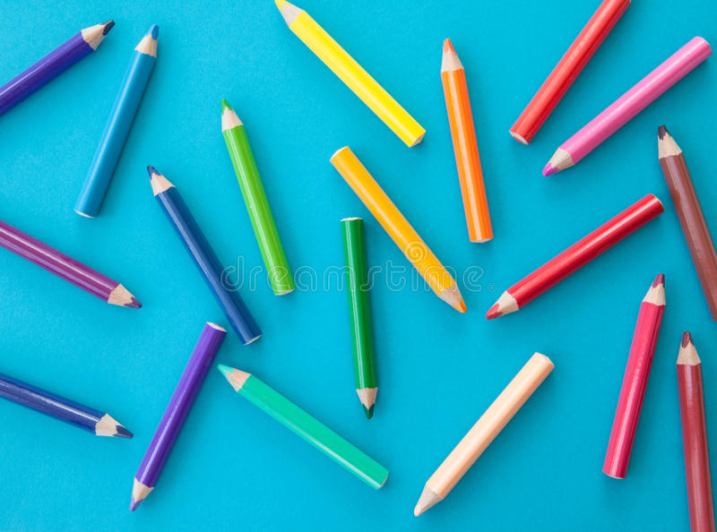 Colorful pens on blue. Colorful pens in colors of the rainbow on blue royalty free stock images