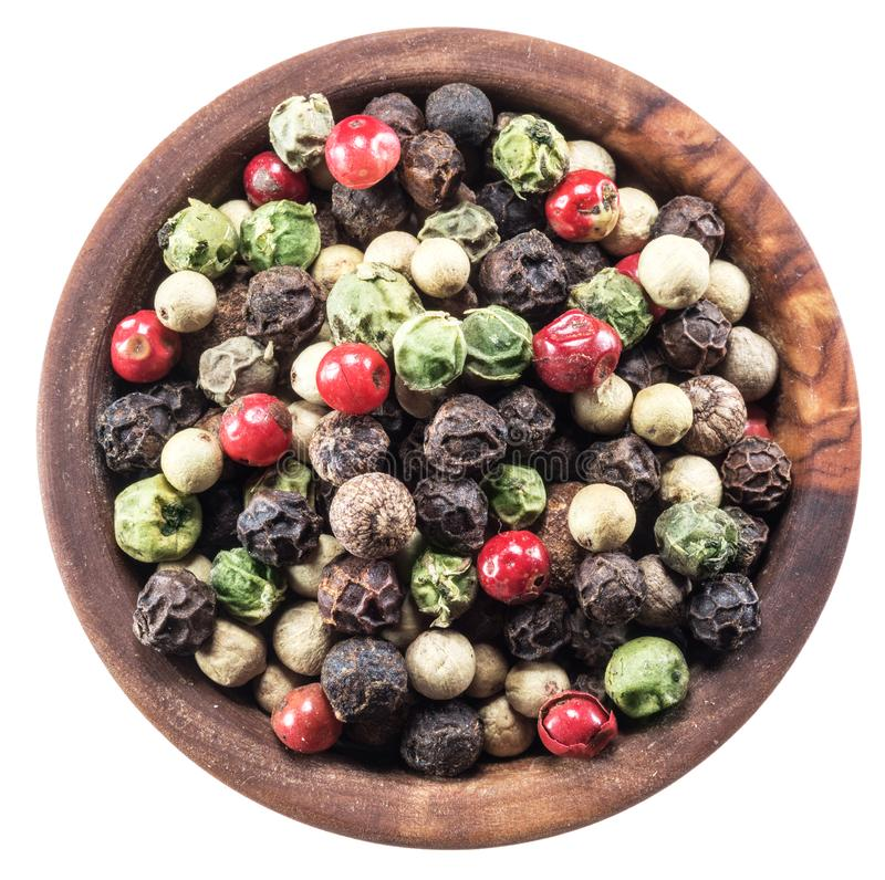 Colorful peppercorns in wooden bowl on white background. Clipping path. Colorful peppercorns in wooden bowl on white background.  File contains clipping path royalty free stock images