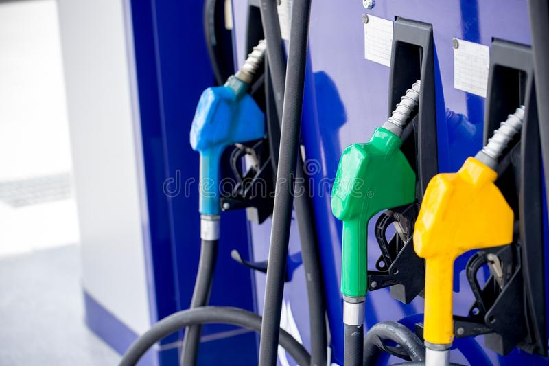 Colorful Petrol pump filling nozzles. On white background , Gas station in a service in warm sunset.Head fuel vehicle refueling facility in asia royalty free stock photo