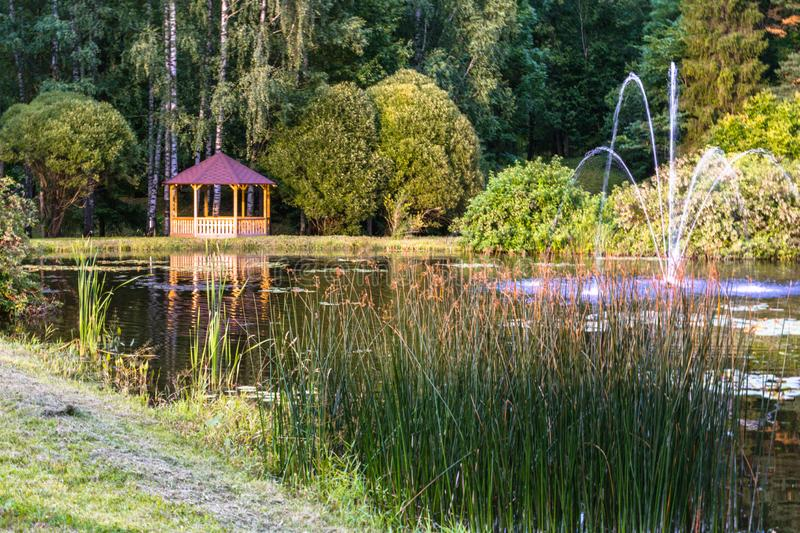 Colorful Photo of the Wooden Summer Garden House in a Park, Between Woods with Blurred Grass Stalks in Foreground - Sunny Autumn. Day, Concept of Peace and stock photo