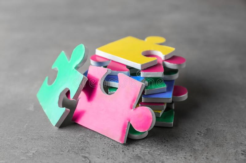 Colorful pieces of puzzle. On grey background stock image