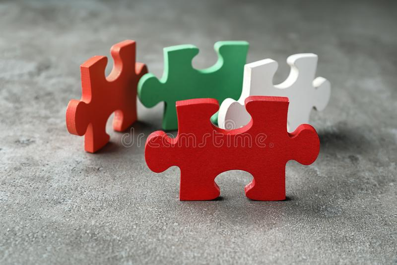 Colorful pieces of puzzle on grey textured background stock image