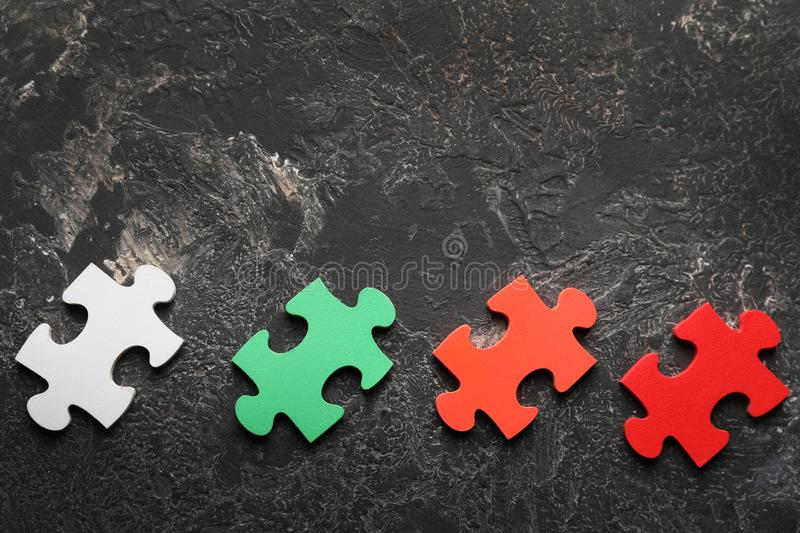 Colorful pieces of puzzle on grey textured background stock images