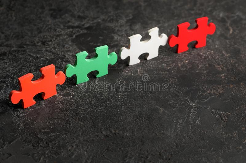 Colorful pieces of puzzle on grey textured background royalty free stock image