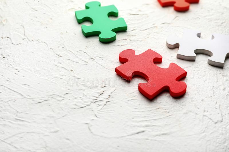 Colorful pieces of puzzle on white textured background royalty free stock photo