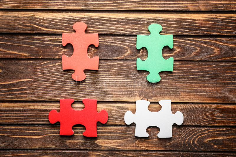 Colorful pieces of puzzle on wooden background stock images