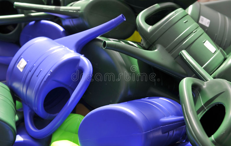 Colorful Pile of Water Cans. Colorful plastic watering cans in a jumbled pile royalty free stock image