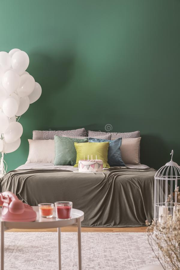 Colorful pillows and birthday cake with candles on king size bed in lovely bedroom, copy space on the empty wall. Colorful pillows and birthday cake with candles royalty free stock photos