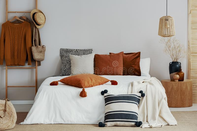 pillows on white bed of classy bedroom with round wooden bedside table and ladder stock photography
